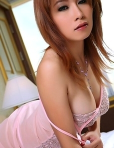 Busty redhead Asian model Jenny Lee removing pink lingerie