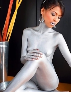 Naomi Chatee sits on a sofa completely covered in silver. This babe has an amazing body and the paint is just a masking agent for her sexiness.