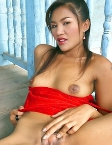Pajar Buabun sits on a porch and she has on a red dress that hugs her body. Her amazing tits are exposed as she rubs on them.